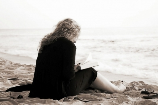 woman-with-blonde-hair-sitting-on-beach-and-reading-book